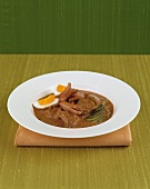 Beef goulash with frankfurters, egg and gherkins
