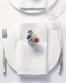 Rustic place-setting with embroidered napkin and flowers