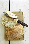 Rustic white bread, partly sliced, on chopping board