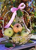 Grüne Äpfel im Henkelkorb mit rosa Schleife