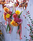 Dahlias and Chinese silvergrass hanging on a fence