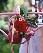 Namensschild, Dahlien und roter Apfel, an Stuhllehne gebunden