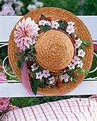Straw hat decorated with clematis wreath on garden bench