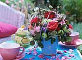 Strauß aus Rosen, grünen Äpfeln, Clematis und Ranken der Glockenrebe auf Teetisch