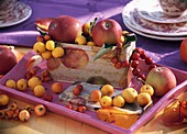 Apples & crab apples in tin with apple motif (table decoration)