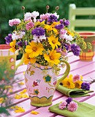 Coreopsis and cornflowers in jug on garden table