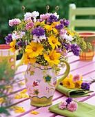 Sommerlicher Blumenstrauss mit Mädchenauge, Kornblumen und Fenchelblüten auf Gartentisch