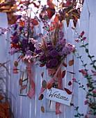 Herbstliche Blumendeko am Gartenzaun mit Schild Welcome