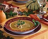 Kürbissuppe mit Mandelblättchen auf herbstlichem Tisch