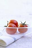 Three tomatoes in glass dish on tea towel