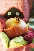 Child's hands in woollen mittens holding pomegranate