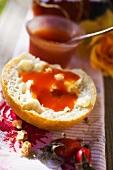 Rose hip jam on bread roll