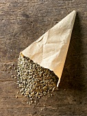 Aniseed in paper bag on wooden background