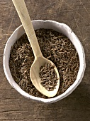 Caraway in bowl with wooden spoon