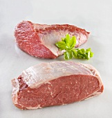Two pieces of fresh beef on marble surface