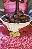 Child's hands in woollen mittens holding bowl of chestnuts