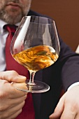 Man swirling cognac in a glass