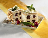 Two pieces of cherry cake with mint and cream