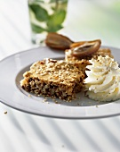 Piece of date tart with sesame seeds and cream