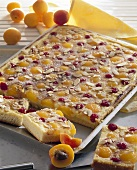 Apricot and cherry cake with flaked almonds on baking tray