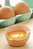 Aufgeschlagenes Ei, dahinter Eier im Eierkarton