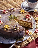 Almond cake with glacé icing and sugar flowers