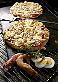 Two egg and shrimp pizzas on baking tray