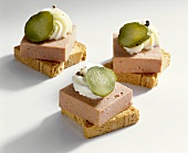 Mini-toasts topped with liver pâté and gherkins