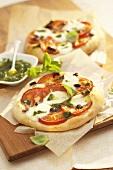 Mini-pizzas with tomato, mozzarella and pesto topping