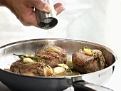 Seasoning fillet steaks in frying pan