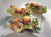 Baguettes topped with steak tartare, egg, sausage & salad