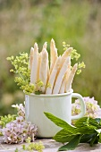 White asparagus in mug with lady's mantle and hydrangeas
