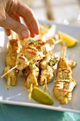 Hand sprinkling grilled chicken kebabs with herbs