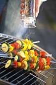 Vegetable kebabs on barbecue being sprinkled with pepper