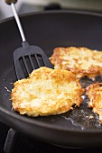 Frying potato rosti in frying pan