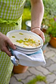 Woman holding plate of gazpacho blanco (cold almond soup, Spain)