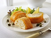 Filled salmon roulade with lemon wedges and capers