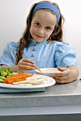 Girl eating raw vegetables with dip