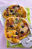 Two vegetable pizzas with sweetcorn and cheese, pizza cutter
