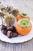 Sweet chestnuts and persimmons on plate