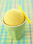 A scoop of mango ice cream in a beaker