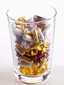Assorted capsules and tablets in a glass