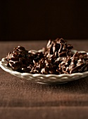 Chocolate-coated almond clusters on white plate