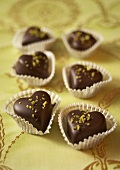 Heart-shaped chocolates with chopped pistachios in sweet cases
