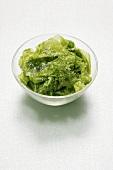 Green seaweed, salted, in glass dish