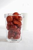 Fresh strawberries in a glass in front of milk bottle