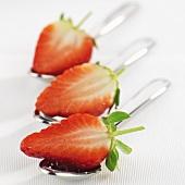 Strawberry halves on three spoons