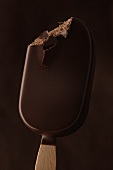 Chocolate-coated ice cream on a stick, a bite taken
