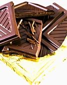 Schokoladenstücke auf Schokoladentafel in Goldfolie
