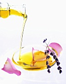 Pouring oil into a dish with rose petals and lavender